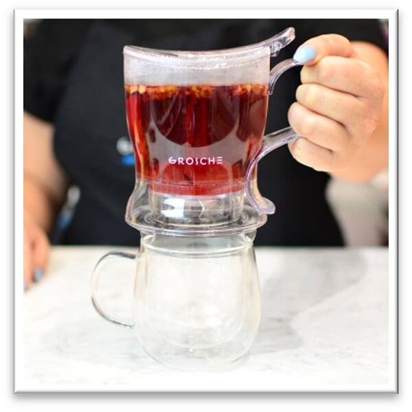 clear plastic gravity steeper containing red tea held over clear glass mug