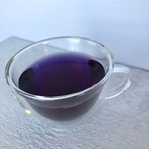 glass teacup filled with Blue to Purple Butterfly Pea Flower infusion