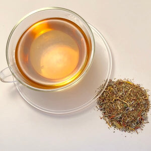amber coloured teacup of mashup teas relaxing deep calm ayurvedic tea and adjacent loose leaf tea