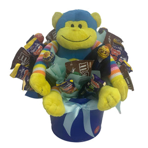 Blue Monkey in a metal tin surrounded by chocolate and lollies