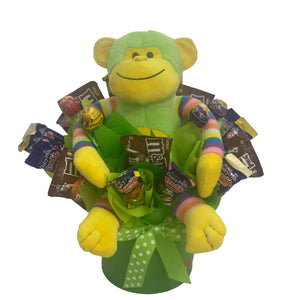 Green Monkey in a metal tin surrounded by chocolate and lollies