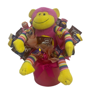 Pink Monkey in a metal tin surrounded by chocolate and lollies