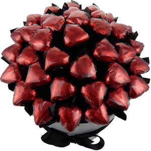 Overhead angle of the red foiled Deluxelicious bouquet with Belgian milk chocolate hearts in a white hat box with black ribbon