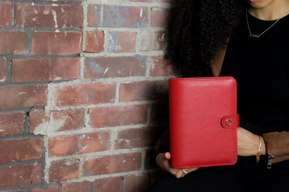 woman holding a5 red leather planner