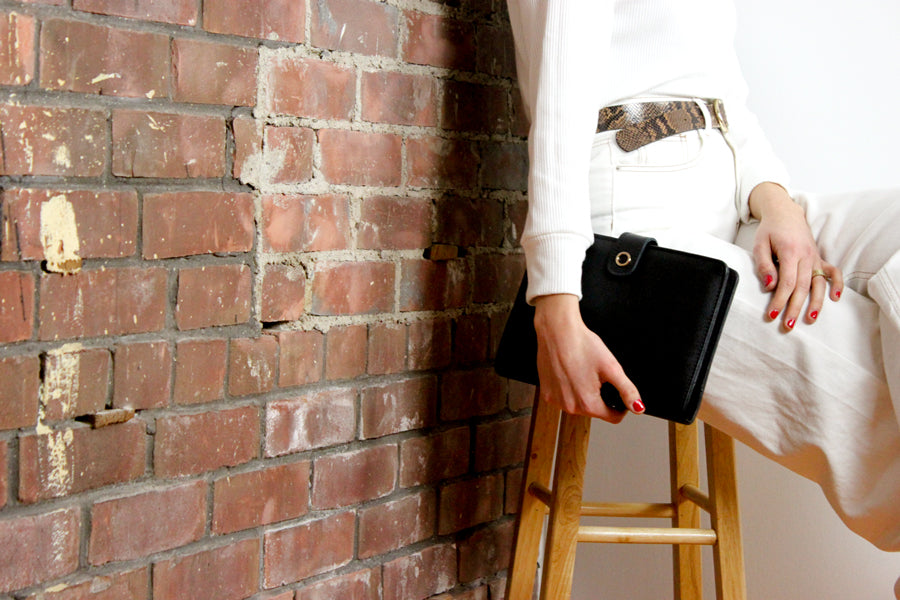 woman holding a5 black leather planner