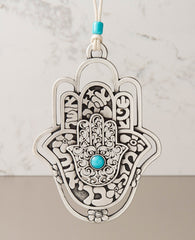 A hanging Hamsa ornament, designed in exquisite beauty: a Hamsa within a Hamsa within a Hamsa. The outer one - a hollow frame decorated by delicate flowers. The middle one - all embossed words of blessing - for abundance, luck, health, happiness and love. The inner one - filigree decoration with a turquoise stone at the center. The ornament is coated in sterling silver and comes with a faux leather string deocorated by a turquoise bead. An impressive and very meaningful gift that is a pleasure to grant to o
