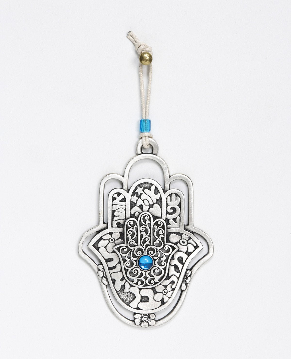 A hanging Hamsa ornament, designed in exquisite beauty: a Hamsa within a Hamsa within a Hamsa. The outer one - a hollow frame decorated by delicate flowers. The middle one - all embossed words of blessing - for abundance, luck, health, happiness and love. The inner one - filigree decoration with a blue stone at the center. The ornament is coated in sterling silver and comes with a faux leather string deocorated by a blue bead. An impressive and very meaningful gift that is a pleasure to grant to our loved o