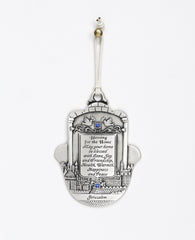 An impressively designed and uniquely decorated Hamsa hanging ornament coated in sterling silver. Decorated with an embossed image of Jerusalem and a pair of peace doves with an olive branch, alongside blessing words of love, joy, laughter and light for the home. Makes a thoughtful and loving gift that will brighten up any house. The Hamsa is embedded with blue Swarovski crystals and a natural colored faux leather string.  Additional languages available: Hebrew and Russian.  Length: 13 cm  Width: 10 cm