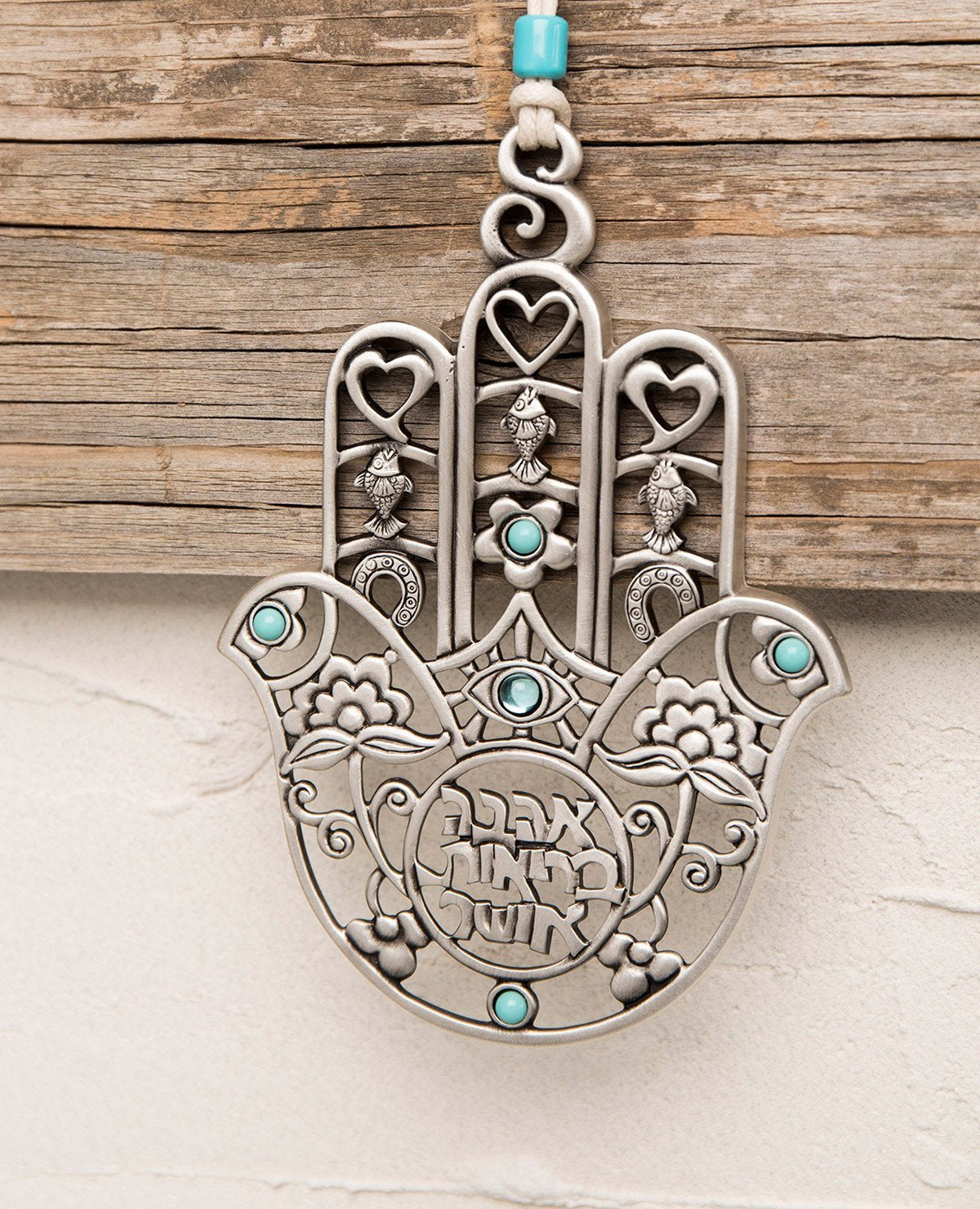 A Hamsa hanging wall ornament, gently designed and full of presence. The more you look at it the more and more you discover details and motifs that intensify its beauty. You can find motifs of a heart, a horseshoe, and a fish... Can you spot the birds? The special cut which creates a variety of different shapes, the intertwined flowers, the turquoise colored stones... in short, a medley of designs and blessings in words and symbols. A gift you will want to gaze at more and more and give again and again. The