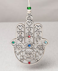 A Hamsa hanging wall ornament, gently designed and full of presence. The more you look at it the more and more you discover details and motifs that intensify its beauty. You can find motifs of a heart, a horseshoe, and a fish... Can you spot the birds? The special cut which creates a variety of different shapes, the intertwined flowers, the coloful stones... in short, a medley of designs and blessings in words and symbols. A gift you will want to gaze at more and more and give again and again. The ornament