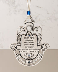 "An impressive and richly designed Business Blessing Hamsa for hanging, coated in sterling silver and embedded with blue Swarovski crystals. The Hamsa comes as a frame and is decorated with motifs of luck, abundance and a blessing for the business with a plate at the center featuring blessings of wealth and livelihood. At the bottom of the plate is an engraved eye embedded with a blue crystal, to protect against the ""evil eye"". A wonderful and exciting gift for anyone with a new or existing business. The orn"
