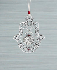 A hanging Hamsa ornament with a delicate filigree like design and a hollow pomegranate hanging at its center. The Hamsa is decorated at its edges with pairs of motifs from the world of good luck charms and blessings, among them a pomegranate, a flower, a fish and a key. All these face each other to multiply the strength of the blessings. Words that bestow prosperity, serenity, blessings, peace and success are written on the pomegranate which hangs from the center of the Hamsa. The ornament is coated in ster