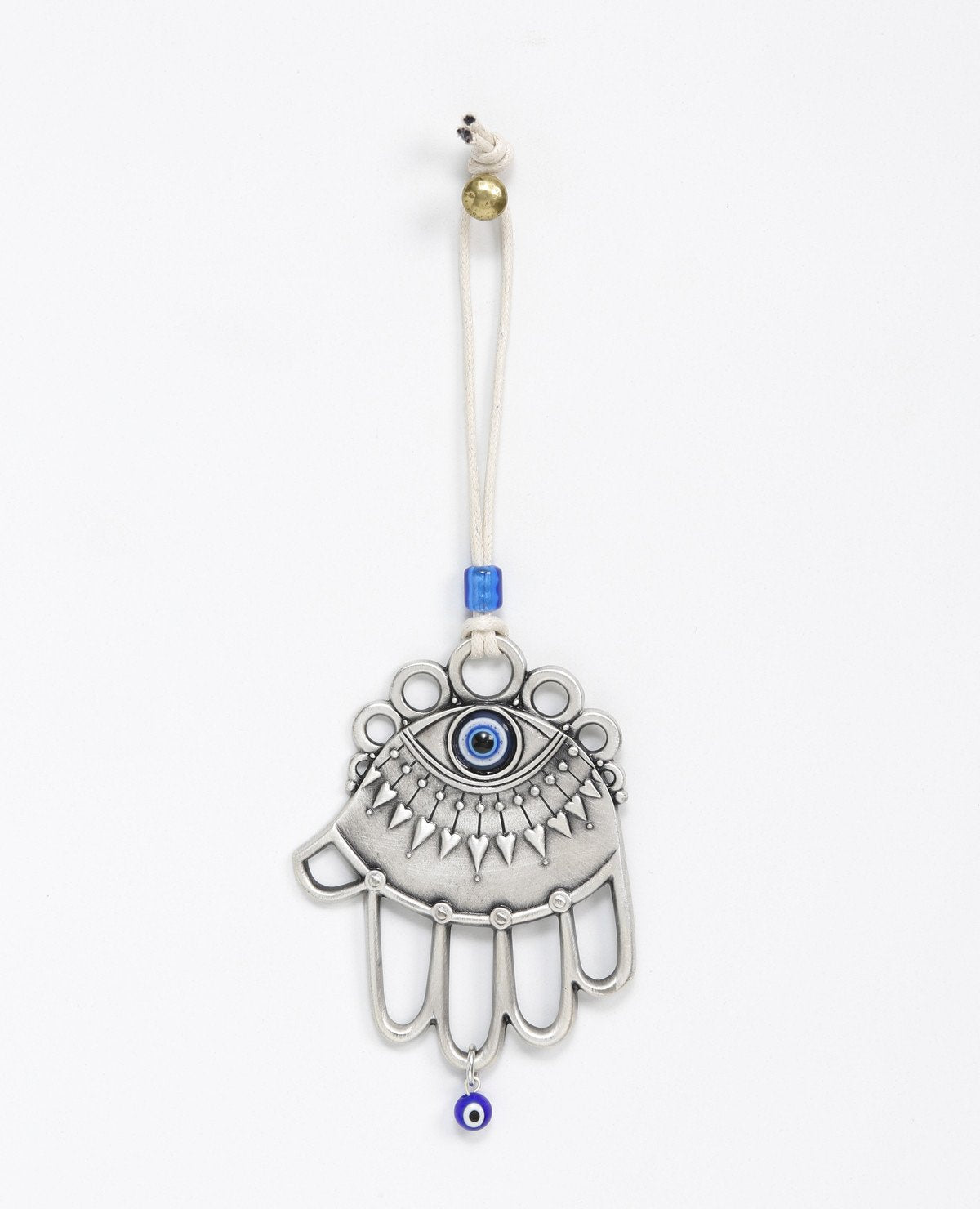 A one of a kind hanging Hamsa ornament. It is designed with a combination of different styles, some of which are hollow, while others are solid decorated surfaces. Embedded at the top of the Hamsa is a large blue eye, decorated by a lower eyelash in the shape of heart arrows. The fingers of the Hamsa are hollow and at their bottom hangs a small blue eye. The ornament is coated in sterling silver and comes with a faux leather string for hanging, decorated by a blue bead.  The blue eye is considered a charm a