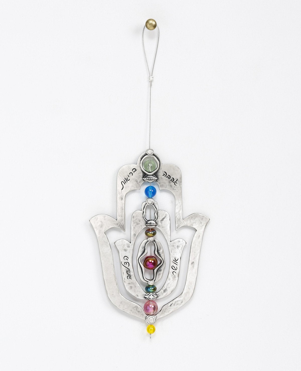 An impressive and neatly designed hanging Hamsa ornament coated in sterling silver. Set on an axis inside a large Hamsa is a smaller Hamsa. The axis is made from a thin string coated in silver and decorated by colorful beads. The ornament spins on the axis, and on each side appear different words of blessing. The qualities of the Hamsa on one side and the power of the words respectively on the other. A great gift that is also a joyful and heartwarming blessing, for any occasion. The ornament comes with a fa