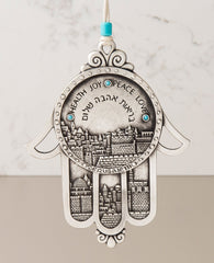 "Wow! What an extraordinarily beautiful gift! A hanging Hamsa ornament coated in sterling silver. The body of the Hamsa along with the three middle fingers are all decorated by an embossed image of the stunning views of Jerusalem. Engraved on the Hamsa in Hebrew and English are the words: ""Health, Love and Peace"" and in English the word ""Jerusalem"". The Hamsa is embedded with turquoise colored Swarovski stones and comes with a natural colored faux leather string for hanging. The string is decorated with a tu"