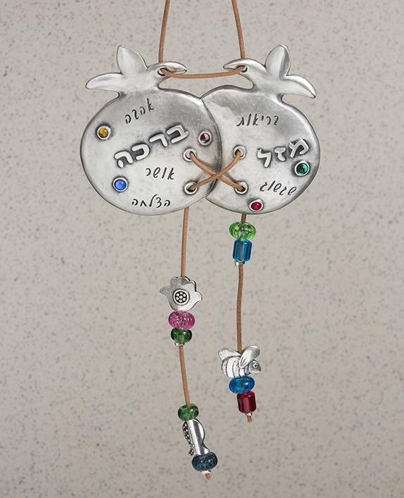 Two are better than one! A sweet and charming hanging ornament with a smile and a blessing. The pair of pomegranates are connected to each other, coated in sterling silver and embedded with colorful stones. A natural colored faux leather string is weaved between the pomegranates, with the ends dangling from the bottom of each, decorated by colorful beads and tiny heart and Hamsa decorations. The top part of the string serves for hanging the ornament. Engraved on the pomegranates are words of blessing: luck,