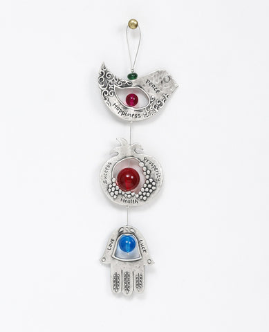 A graceful seven blessings hanging ornament coated in sterling silver, that brings joy and blesses. The ornament is made up from three motifs from the world of charms: a bird, a pomegranate and a Hamsa. All are connected to each other by a thin silver coated string decorated by colorful beads, with a loop at the end for hanging. Each motif is designed with unique decorative embossments, and together create a charming and harmonic whole. Written on each one of the shapes are words of blessing, in Hebrew on o