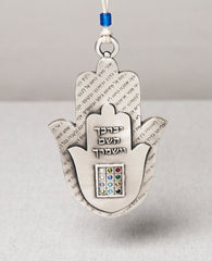 "The priestly breastplate Hamsa ornament will very much excite whoever shall receive it. It is designed as two Hamsas, one on top of the other. Written on the Hamsa in the background is an excerpt from the second chapter of the ""Shema Israel"" prayer. The inner Hamsa is designed as a smooth plate with the passage ""May the lord bless you and keep you safe"" embossed on it. Beneath, the priestly breastplate is embossed and inlaid with stones in the same colors as the breastplate stones. The passage ""May the lord"