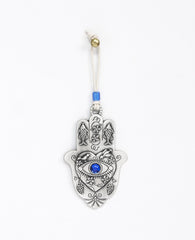 "A hanging Hamsa ornament packed with goodness! The Hamsa is coated in sterling sivler and comes with a natural colored faux leather string for hanging, decorated by a blue bead. At the center of the Hamsa is a big heart with an embossed eye inside embedded with a blue colored stone (against the ""evil eye""). Above the eye are chirping birds (of peace and love). The Hamsa is decorated with embossed fish (for luck), as well as vine leaves and grape clusters (for abundance). What else could we ask for? Just the"