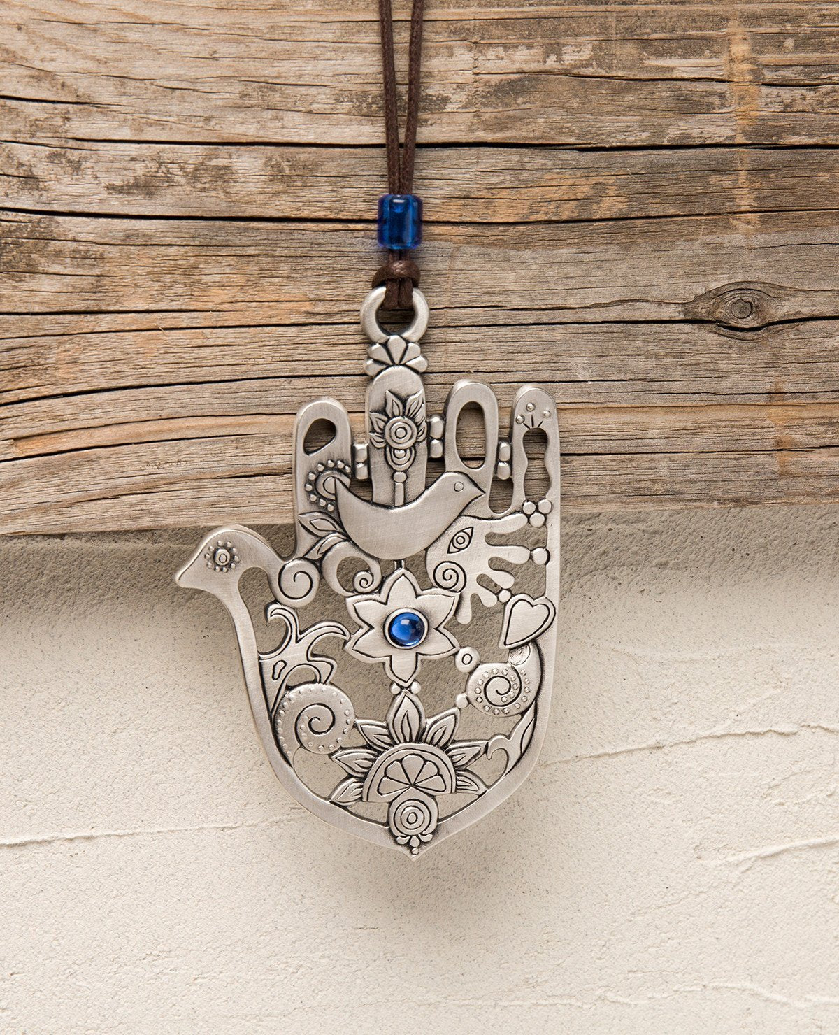 A subtle, authentic and artistically designed Hamsa hanging ornament. The Hamsa is coated in sterling silver and is designed as spaces and embossments of blessing motifs. At the center of the Hamsa is a flower inlaid with a blue Swarovski stone and above it an embossed dove. The thumb of the Hamsa is designed as the head of a dove and the ornament in its entirety resembles the shape of both a Hamsa and a dove. This is a charming and blessed hanging ornament that combines the qualities of the Hamsa for luck