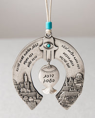 An originally and authentically designed hanging horseshoe Business Blessing. The horseshoe is decorated on both sides with an embossed image of Jerusalem. In the middle hangs a pomegranate with a Hamsa on top embedded with a turquoise colored Swarovski crystal. The hanging ornament is coated in sterling silver and decorated with blessing words for abundance, success and good fortune. Made to grant its receiver with love, good intention and a heartfelt blessing. Comes with a natural colored faux leather str