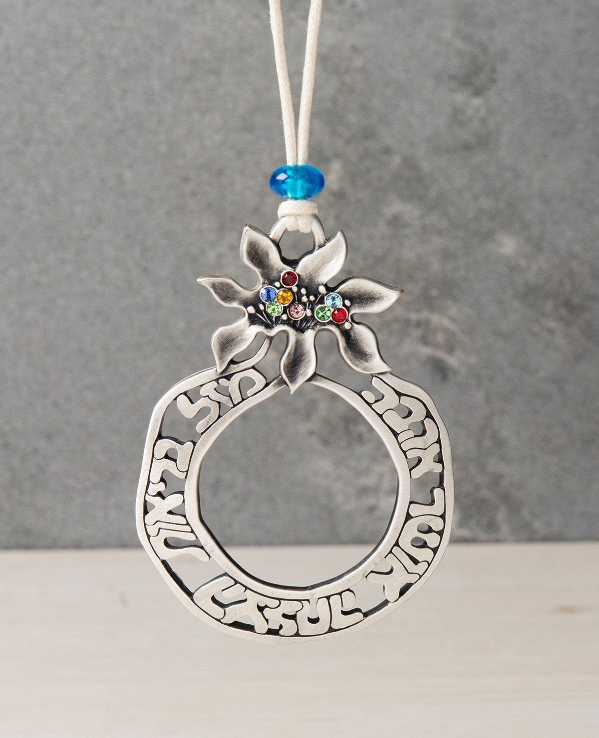 A beautifully designed Azure pomegranate hanging ornament with a Home Blessing. The pomegranate is coated in sterling silver, hollow at the center and its edges are decorated with the blessing words of: luck, health, success, happiness and love. The crown of the pomegranate is embedded with colorful Swarovski stones which create a rich and extravagant look. Makes a great gift to also grant the blessing of the pomegranate, one of abundance and privilege, and also the power of the blessing words engraved on i