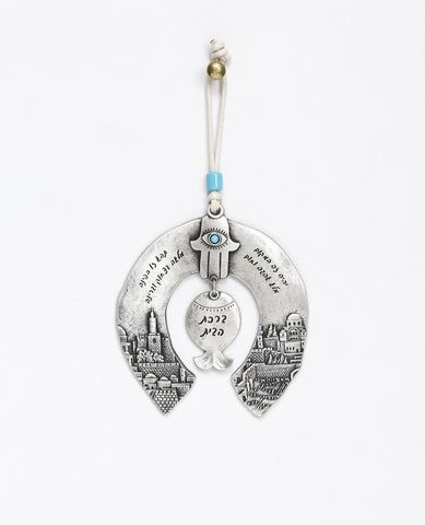 A unique and originally designed hanging Home Blessing ornament in the shape of a horseshoe. The horseshoe is embedded with an embossed image of Jerusalem on both sides. A pomegranate hangs from the center, with a Hamsa on top of it inlaid with a turquoise colored Swarovski crystal. The ornament is coated in sterling silver and decorated with words of blessing, love and light. Comes with a natural colored faux leather string decorated with a turquoise colored bead. Makes a great housewarming gift or an orig
