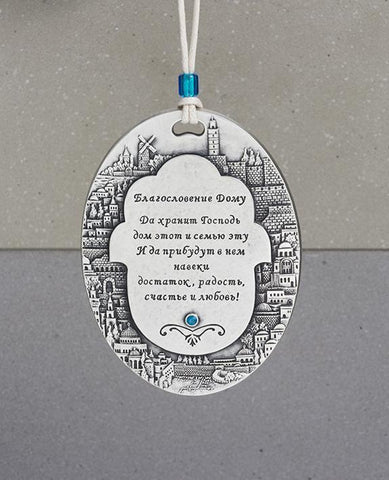 A spectacularly beautiful hanging Home Blessing ornament in Russian, in the shape of an oval plate. The plate is embedded around its edges with an outline of the sights of Jerusalem, and in the center a Hamsa upon which appear blessing words for love, friendship, joy, health, happiness and peace. Makes a very welcoming gift for the home intended for the people we hold dear, far or near. The hanging ornament is coated in sterling silver and embedded with a blue colored Swarovski crystal. Comes with a natural