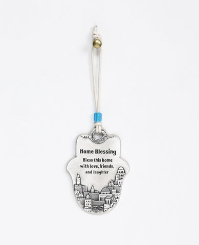 A Hamsa shaped hanging Home Blessing ornament coated in sterling silver and decorated with an embossed image of Jerusalem. The words of blessing will bestow the house with health, peace, kinship, abundance and fulfilled dreams. A joyful and thoughtful gift that blesses anyone who may receive it. Comes with a natural colored faux leather string for hanging decorated with a blue colored bead.  Additional languages available: Hebrew.  Length: 9 cm  Width: 6 cm