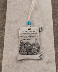 A hanging Home Blessing ornament in the shape of a scroll, coated in sterling silver and decorated with a beautiful embossed image of the city of Jerusalem. The scroll shaped design connects us back to ancient times, which already then the power of words were acknowledged as a force that can manifest abundance and joy in our life. The hanging ornament comes with a faux leather string decorated with a blue colored bead.   Length: 9 cm  Width: 5 cm