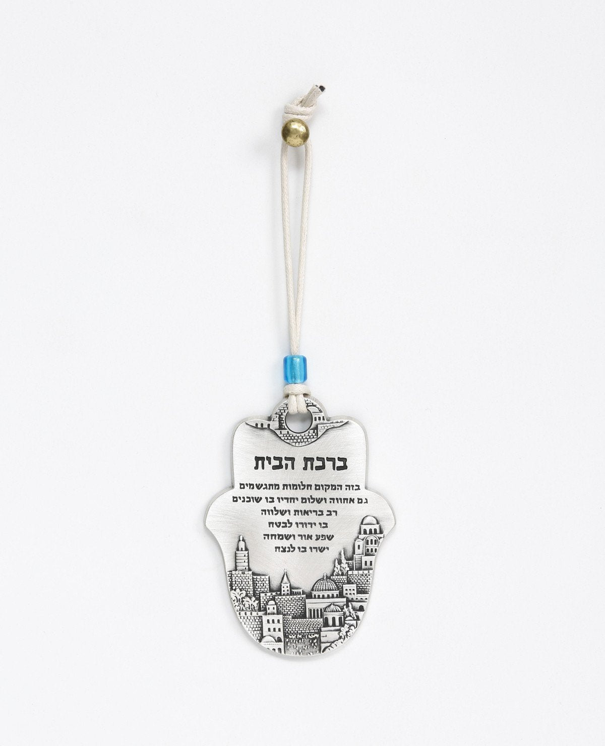 A Hamsa shaped hanging Home Blessing ornament coated in sterling silver and decorated with an embossed image of Jerusalem. The words of blessing will bestow the house with health, peace, kinship, abundance and fulfilled dreams. A joyful and thoughtful gift that blesses anyone who may receive it. Comes with a natural colored faux leather string for hanging decorated with a blue colored bead. Additional languages available: English.  Length: 9 cm  Width: 6 cm