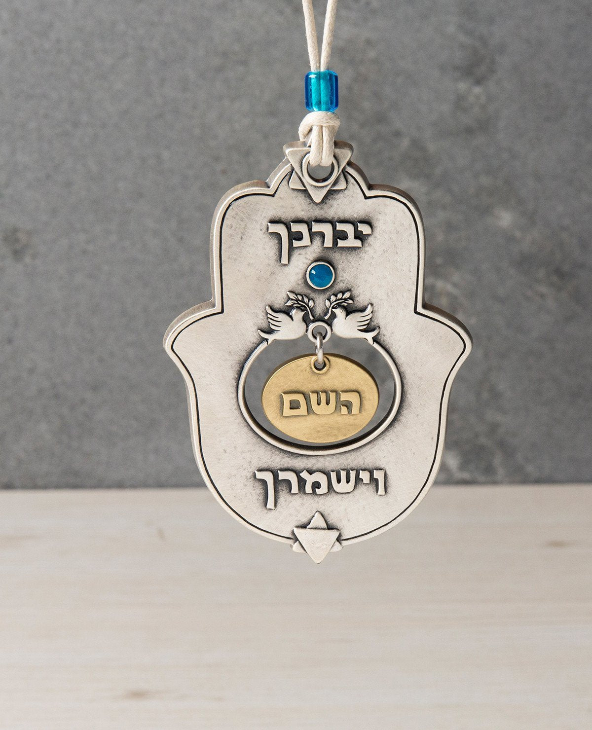 "A designed hanging Hamsa ornament that carries on it the blessing of ""May the Lord bless you and keep you safe"", words that were added to the Kohen's blessing out of Jacob's blessing before his death to Joseph's sons - Ephraim and Manasseh. The Hamsa is coated in sterling silver combined with brass and has the blessed sentence embossed. Embedded at the center is a blue Swarovski stone and a pair of doves with an olive branch. At the top and bottom of the Hamsa are Stars of David. The Hamsa hangs from a natu"
