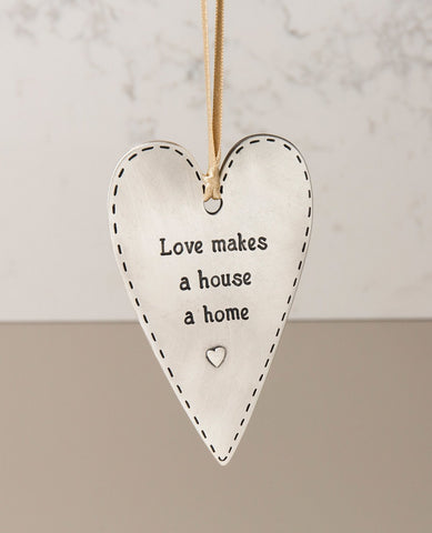 "A ""love makes a house a home"" hanging ornament designed in the shape of a gracefully decorated heart and coated in sterling silver. Because what else turns walls and a roof into a home if not the love that dwells within them? Designed as an elongated heart shaped plate, on one side is the above sentence in English and a small embossed heart, and on the other is a pair of embossed loving hearts. The ornament comes with a natural colored faux leather string. Elegantly and cordially designed, it makes for a ch"