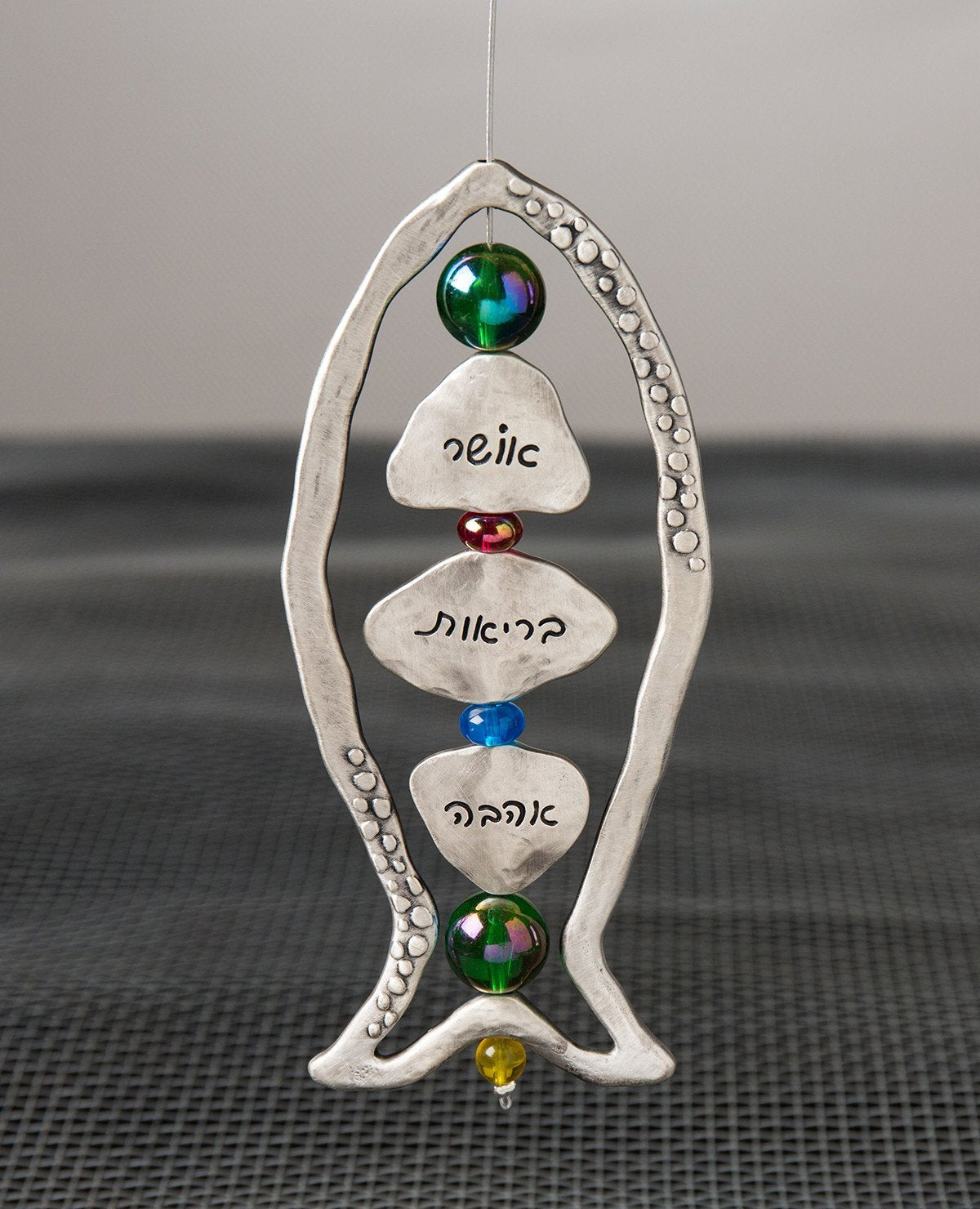 "Happiness, health, love! What else could we ask for? A large sterling silver coated hanging ornament in the shape of a fish, with a beautiful design that focuses on generosity. The frame of the fish is hollow and decorated by pretty embossments on its sides. At the center of the fish, upon a thin silver rod, blessing charms are thread with colorful beads in between them. The words ""happiness"", ""health"" and ""love"" are engraved on the charms in Hebrew on one side and in English on the other. The silver rod co"
