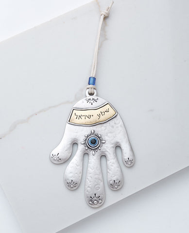 "A charming and inspiring Hamsa hanging wall ornament, coated in sterling silver and brass. It hangs from a natural colored cotton string decorated with a blue bead. The rich and stylish design and the word of ""Shma Israel"" in Hebrew make a wonderful gift that contains beauty and protection. Grant it with love (and don't forget to spoil yourselves as well). Length:14 cm Width: 10 cm"