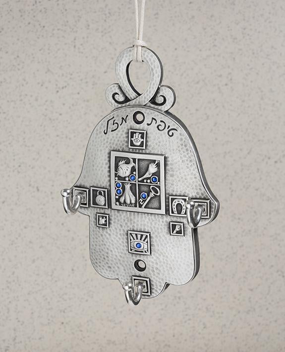 A large and impressive Hamsa with hooks meant for hanging your belongings. The Hamsa is coated in sterling silver and embedded with blue colored Swarovski crystals. The Hamsa is decorated with embossed geometric shapes that have motifs inside them symbolizing abundance, fertility, luck, and protection. On the Hamsa are three strong hooks for hanging your things, and a built in loop is placed on the top for hanging the Hamsa. Makes for a very impressive, useful and blessed gift, for a new home, in the entran