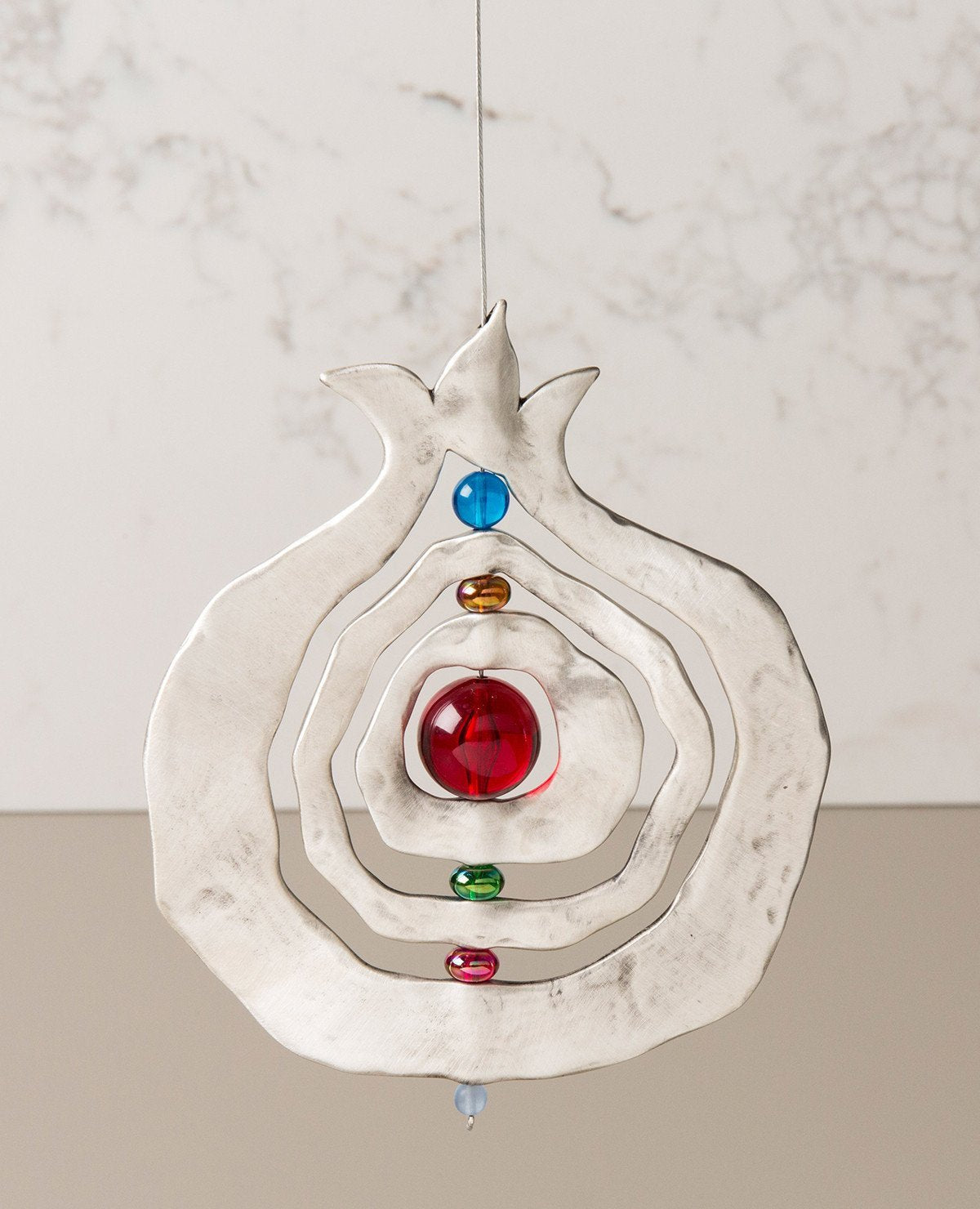 A pomegranate hanging ornament with a unique design that grants it motion which hypnotizes the eye with beauty. The pendant is designed in the shape of a hollow pomegranate with circular shapes at its center which are thread around one central axis, with colorful beads between them. The pendant is coated in sterling silver and hangs from a thin and strong silver string. Always suitable as a unique gift, embodying within it the pomegranate's blessing of abundance and fertility. Especially suitable around Ros