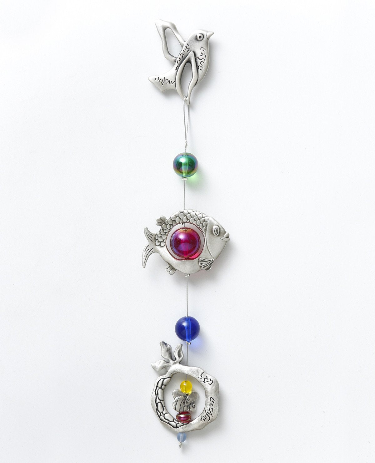 A delicate and beautiful hanging wall ornament, bringing together a few blessing motifs: a bird, a fish and a pomegranate, all hanging from a subtle silver string. The ornament is coated in sterling silver and is decorated with colorful beads. The bird and pomegranate are engraved with words of blessing for harmony, luck, success, stability, and joy. Makes a charming gift for any occasion and for anywhere in the house or office. It's so pleasant to gaze at this lovely ornament and smile every moment with gr