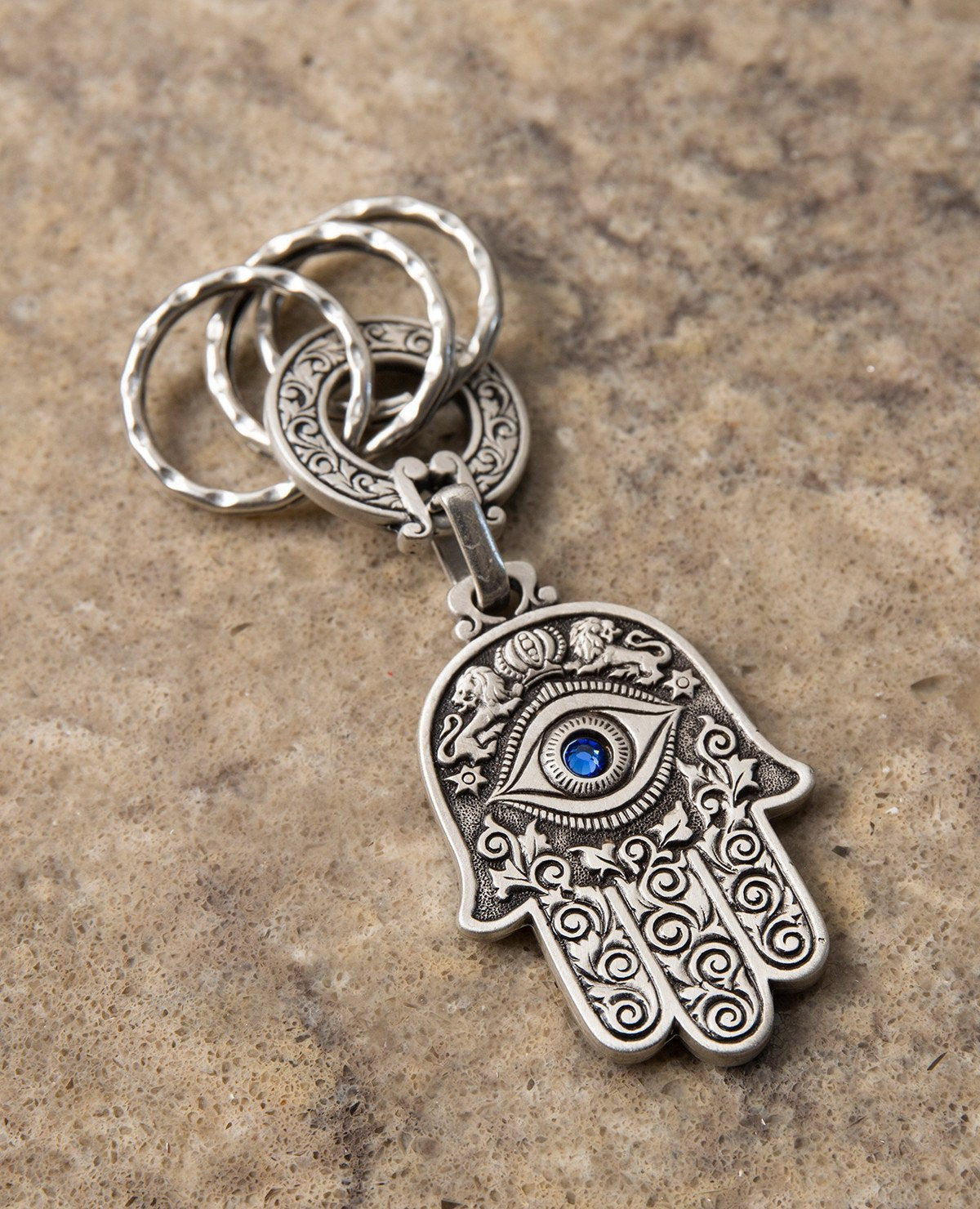 A double sided Hamsa keychain coated in sterling silver. On one side is a big eye embedded with a blue colored Swarovski crystal and embossed lions. On the other side are embossed birds, pomegranates, fish and grapes. The whole Hamsa is decorated in a filigree like style. The connecting links and the key rings are massive and strong. It's fun to connect our most important keys to it and most definitely to grant our loved ones with such a beautiful Hamsa, blessed with the many icons of good fortune, protecti