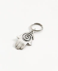 A charming and uniquely designed Hamsa shaped keychain which incorporates a full design with the empty spaces within the spiral. The Hamsa is coated in sterling silver and is slightly concave. It is so beautiful that you can just keep staring at it over and over, feel its different textures and sense the blessing within. A strong and reliable keychain that makes a great gift for your loved ones.  Length: 7 cm  Width: 4 cm