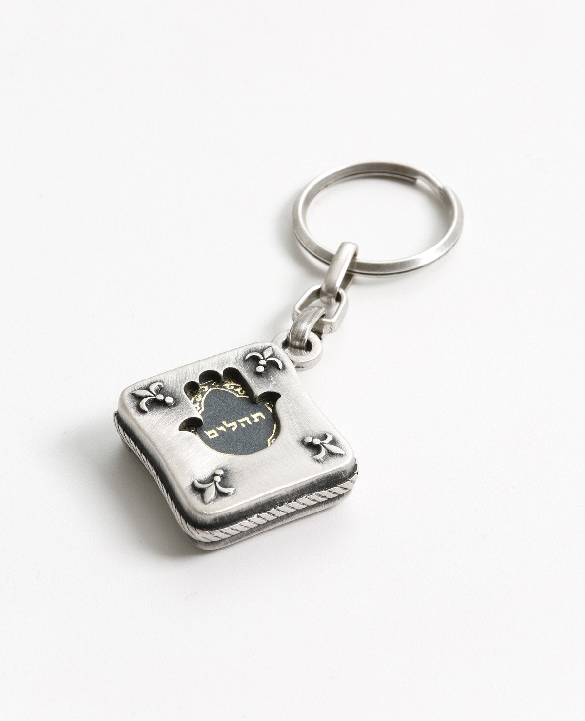 Tehillim is always with you. An exciting and elegantly designed keychain coated in sterling silver. Fashioned in the form of a small silver envelope with the book of Tehillim inside. The outline is designed on both sides as a frame with a hollow Hamsa shape in the middle, through which we can see the book on both its front and back sides. Feel safe and connected to your roots any time you have this wonderful keychain on you. You will feel even better when you grant it with love to the dearest people in your