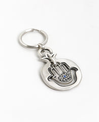 "A blessing every time you open and lock. A charming keychain coated in sterling silver and carrying a blessing that follows you wherever you go. A Hamsa hangs within the hollow pomegranate frame. On it's one side an eye embedded with a blue colored crystal and a charm against the ""evil eye"", and on the other side appear the words ""Hamsa On You"" decorated with flowers, for luck and blessing. All of these are contained within the pomegranate, which brings the blessings of abundance and fertility. A suitable a"