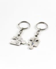 A pair of originally designed keychains, surprising and exciting, coated in sterling silver. The keychains are designed as two pieces of a puzzle that complete each other. On each keychain part of a love sentence is inscribed, with the completing bit on the other piece. The keychains are embedded with colorful Swarovski crystals. Will you find your missing piece of the puzzle? Or grant it as a gift of love to your favorite couple? We warmly recommend either!  Length: 6 cm  Width: 4 cm