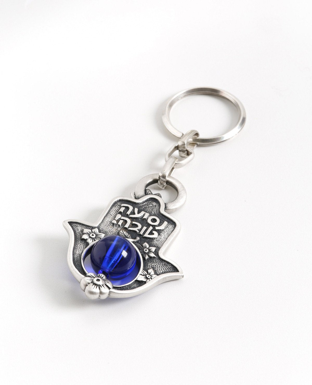 "A delicate and charmingly designed Hamsa keychain. The Hamsa is coated in sterling silver and has a stunning blue bead which can be seen from both sides of the Hamsa threaded on its bottom part. On the one side is a delicate flower decor with the embossed words ""Bon Voyage!"" while the other side is decorated with flowers and a pair of fish. The keychain is strong and reliable. Makes a great present for anyone whose vehicle's keys are in need of a pretty holder. Blessed with the Hamsa charm against the ""evil"
