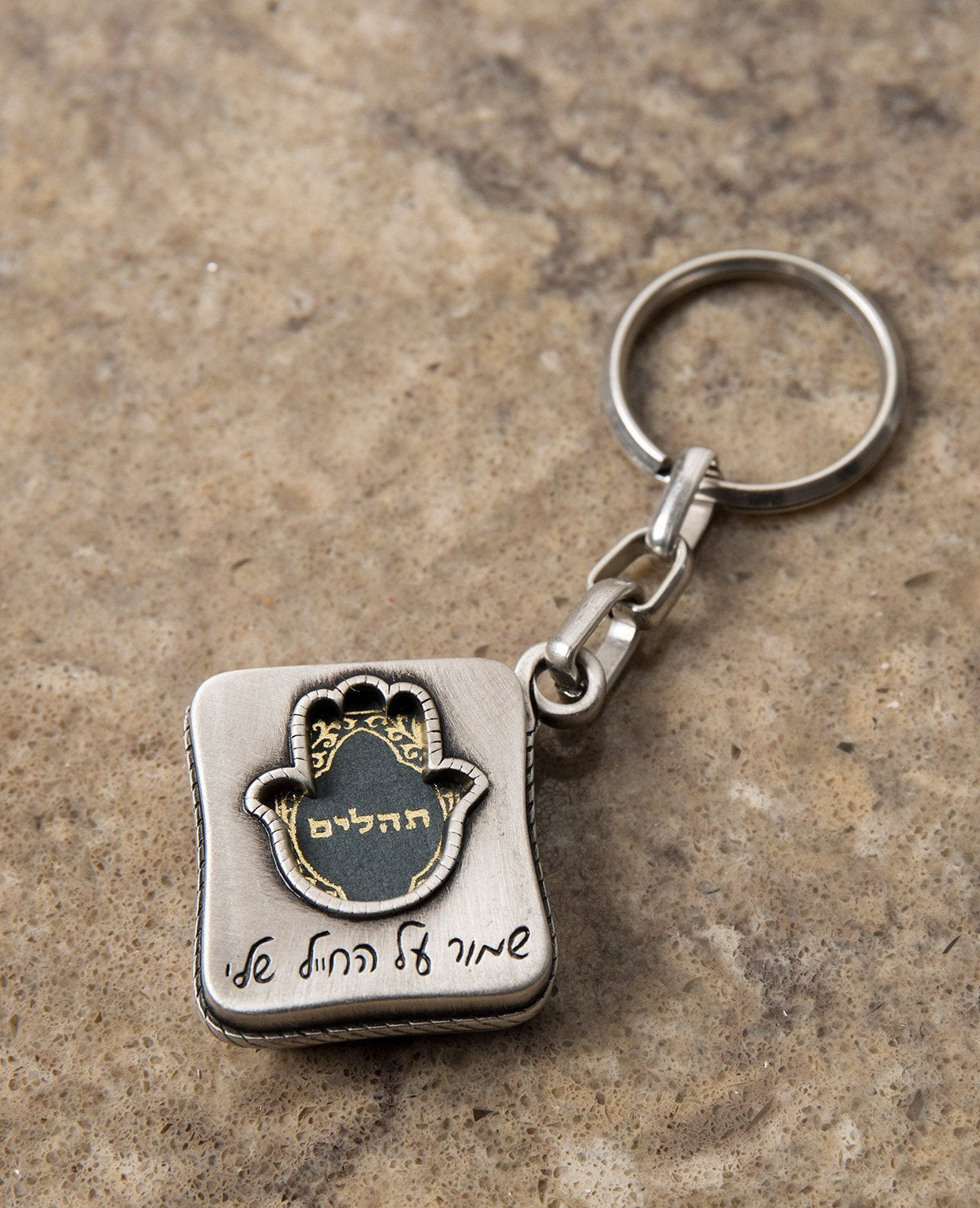 "All the love, worry, values and protection in one place. The keychain is designed in the shape of a box, within it a small book of Tehillim for the way. Embossed on one side of the keychain is a hollow Hamsa, which the book can be seen through, and the words ""protect my soldier"" engraved at its base. On the other side is an embossed caricature of a soldier on guard next to a flag of Israel. The keychain is coated in sterling silver and is strong and reliable. Make sure it is always in your soldier's pocket!"