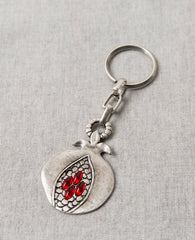 "It's impossible to not marvel over its sheer beauty. The keychain is designed as an artistic and unique looking pomegranate. On one side is an embossed image of a pomegranate sliced open to show its seeds, with red stones in the shape of the seeds. Engraved on the other side is the blessing: ""abundance, blessing and success on your journey"". The pomegranates virtue of abundance and privilege always accompanies whoever will carry their keys on this charming keepsake. The keychain is coated in sterling silver"