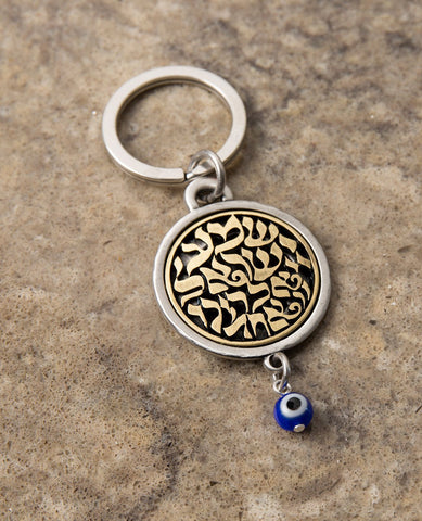 "A keychain that touches the soul of any Jew. Designed as a circle, with the embossed words ""Hear O Israel, the Lord our god, the Lord is one"" in brass coated letters on a black background on one side. Engraved on the other side is the sentence ""with the greatness​ of thy powerful right hand"", decorated by a Hamsa with an eye. At the bottom of the circle hangs a blue eye - against the ""evil eye"". The words ""Shema Israel"" remind the people of Israel that God is the one and only and is regarded in Judaism as t"