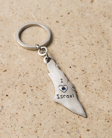"A charming keychain for Israel lovers, in English and designed in the shape of a map of Israel. Engraved on one side are the words ""I Love Israel"" with a heart embedded with blue colored Swarovski crystals, and on the other side a flag of Israel. The keychain is coated in sterling silver and is strong and reliable. This reminder of the simple love for Israel makes a great gift for friends and family in Israel and abroad.   Length: 7 cm  Width: 2 cm"