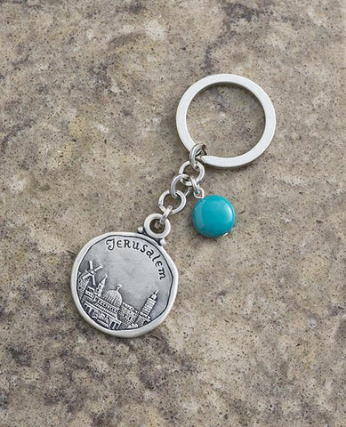 "An exciting keychain that keeps Jerusalem close to us at all times. Designed as a circle, on one side appears the Jerusalem landscape as well as the word ""Jerusalem"", and on the other side another view of Jerusalem. Connected to the top of the circle is a chain with a beautiful turquoise stone hanging from it. The keychain is coated in sterling silver and is strong and reliable. Makes a great gift for family and friends in Israel and abroad who we wish to grant with a souvenir from our one and only Jerusale"