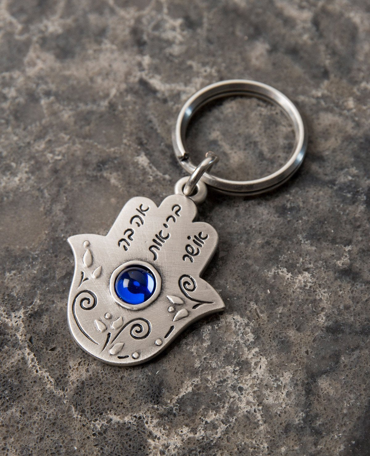 "Someone is thinking good thoughts about you... A beautiful and unique Hamsa shaped keychain that will simply warm any heart. Engraved on one side of the Hamsa, between floral decorations, is the sentence ""Someone is thinking of you"". The other side is embedded with a round blue colored stone and is engraved with the words: ""Love, Health, Happiness"". We read your mind and designed this perfect gift especially for you, allowing you to pass on your loving thoughts in the most original way. The keychain is coat"
